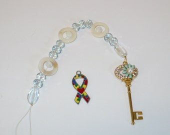 Golden key suncatcher with mother of pearl and crystals.
