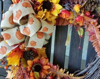 Fall grapevine floral wreath with pumpkin burlap bow.