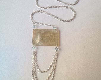 200 year old Antique Chinese mother of pearl gaming chip pendant on sterling silver chain accented with faceted blue topaz stones.