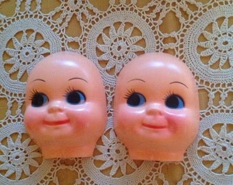 """Two 4 5/8"""" plastic celluloid-like doll faces"""