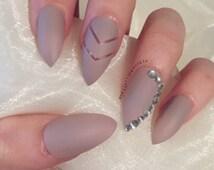 Matte nude stiletto false nails with chevron negative design and rhinestone design