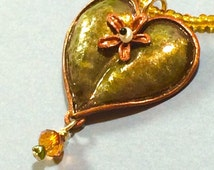 Lustrous bronze floral heart pendant on seed bead necklace. Brass, F.W. Pearls, bronze crystal, G.F.findings.