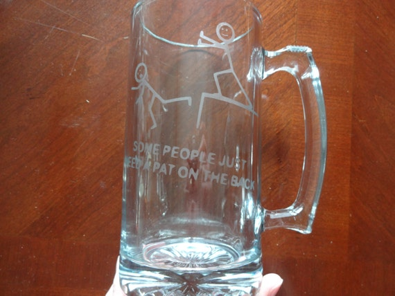 "Glass etched beer mug with ""Some people just need a pat on the back"" etched on it with stick figure pushing another stick figure off a cliff"