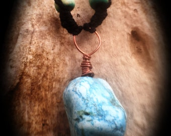 Large Turquoise stone with copper wrap on a hemp cord with wooden beads.