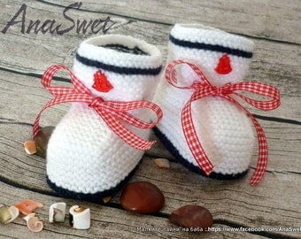 Knitted baby booties/slippers/shoes in white with a red satin ribbon