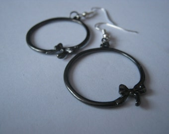 large black hoop earrings with a small bow at the bottom