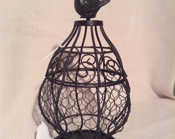 Black Decorative bird cage with bird on top.