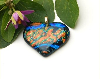Fused dichroic glass pendant heart shape, with blue stripes, gold and green on black background