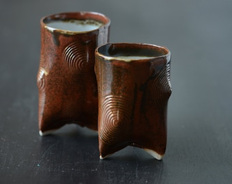 Reddish hand built his and hers tripod cups in porcelain with  concentric circular design