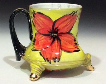 Red yellow flower mug with black handle and gold toes