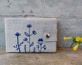 Horizontal Moleskine cover with embroidered wild flowers. Embroidered cover in sand and blue made of organic fabrics