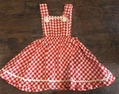 Sweet late 1940s or early 1950s vintage red and white gingham girls pinafore or jumper dress with rickrack trim
