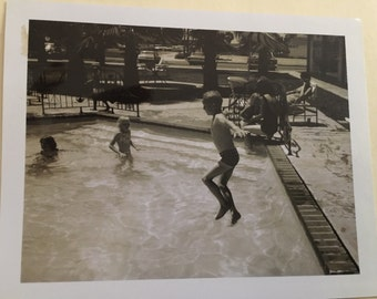 Vintage black and white photo - 1950s - Young boy jumping into swimming pool