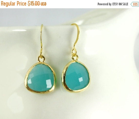 15 OFF. Aqua blue earrings opaque-ish with gold bezel setting. Framed and faceted
