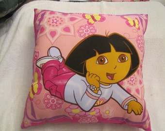 "Dora the Explorer Pillow; Same design on both sides of the pillow; 17"" x 17""; 100% cotton with polyfill stuffing"