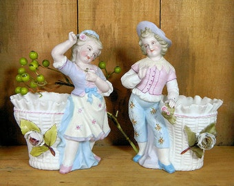A Pair of Antique Bisque Figural Spill Vases Boy and Girl with Baskets