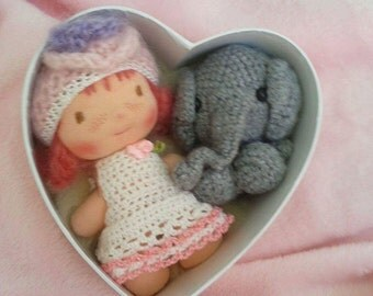 Flora and her elephant,a  Waldorf little doll inside a heart.