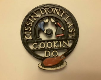 Vintage Antique 1960 black iron trivet kissing don't last cooking do