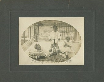 Cute children posing w iron bicycle tricycle and doll antique photo