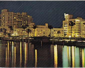 Vintage 1978 Postcard Night Scene of Hotels Along Indian Creek at Tropical Miami Beach, Florida