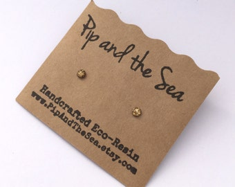 New improved waterproof design! Itty bitty, golden galaxy eco-resin studs on allergy-friendly surgical steel.