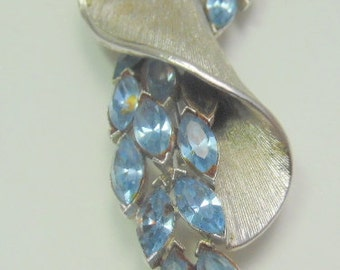 Brushed silver scroll shaped brooch with deep blue rhinestones