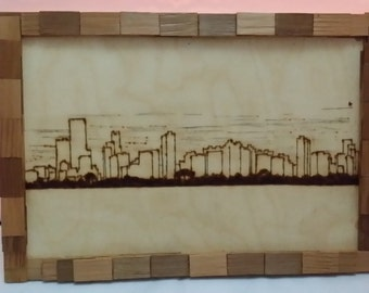"SKYLINE pyrography picture in a ""brick"" effect frame"