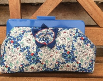 Blue floral clutch purse with blue resin handle, internal pocket and hand. made barkcloth fabric flower decoration.