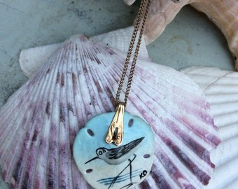 Sand dollar miniature with hand painted sand piper bird. Blue and white with gold tone chain. Vintage