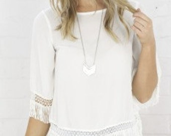 A relaxed white top with fringes