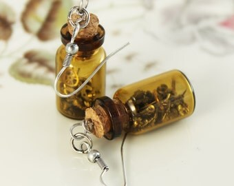 Handmade earrings, composed by vintage metal watch parts inside a vial.