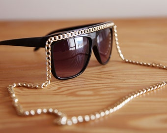 Vintage black plastic sunglasses with gold chain.