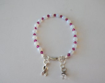 Beaded cancer awareness bracelet in white opal and fuchsia crystals with silver charm