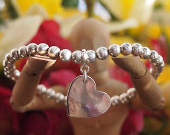 A cute simple little heart charm handmade in fine silver on a sterling silver bead stretch bracelet ....