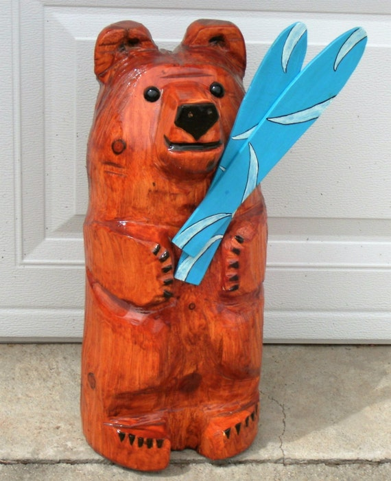 Chainsaw carving bear holding skis by cactusflatscarvings