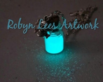 "Aqua Blue Glow In The Dark ""Radioactive"" Sand Mini Glass Bottle Jar Necklace with Silver Skull & Cross Bones on Silver Crossed Chain"