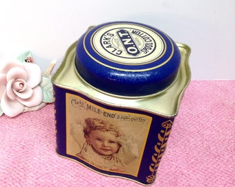"""CLARK'S SPOOL COTTON Tin is a Vintage 4 1/8"""" Sq. Tin Canister with 2 Illustrations of a Child on Opposite Wavy Sides & Clark's Cotton on Lid"""