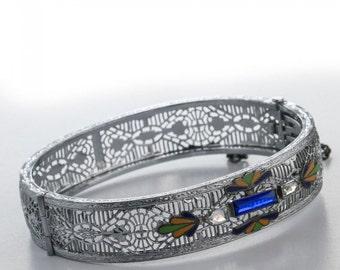 Superb Art Deco hinged rhodium filigree bangle bracelet with enamel and glass stones. c. 1930. (brad114)