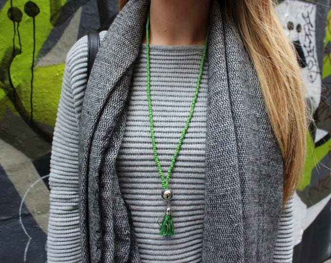 Green tassel necklace with silver ball feature.