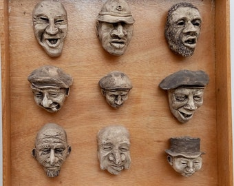 """Ceramic wall hanging artwork, Unique, one of a kind. Clay sculpture on a wood surface,, ceramic faces. title:""""hard working  people"""""""