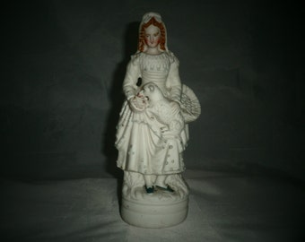Parian ware figurine of girl holding a lamb. 19th century parian shepherdess decorated with glass beading.