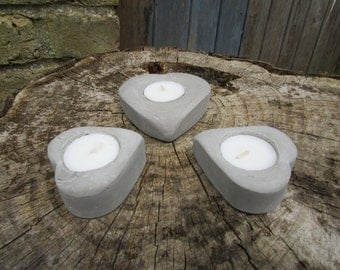A set of three heart-shaped concrete tealight holders