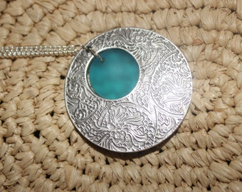 silver medallion with sea glass