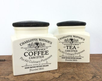 Pair of vintage black and cream ceramic tea and coffee storage jars with wooden lids
