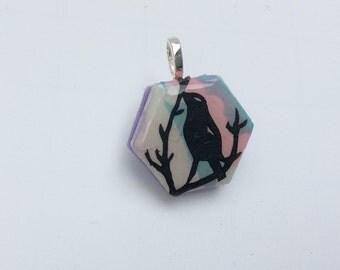 Papercut art pendant featuring a miniture papercut of a blackbird in a tree