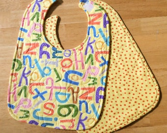 "Quilted baby/toddler bib - yellow abc print, velcro closure, reversible, 10"" x 13 1/2"""