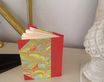 Small handmade notebook, 24 pages. Hand sewn pages bound in quarter red book cloth and hand made marbled paper.