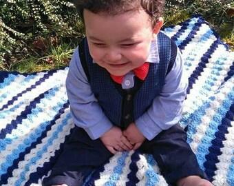 Corner-to-corner hand crocheted baby blanket with scallop edging. Machine washable. Navy, blue, and cream