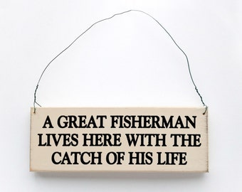 Wood Sign Saying A Great Fisherman Lives Here With The Catch of His Life.