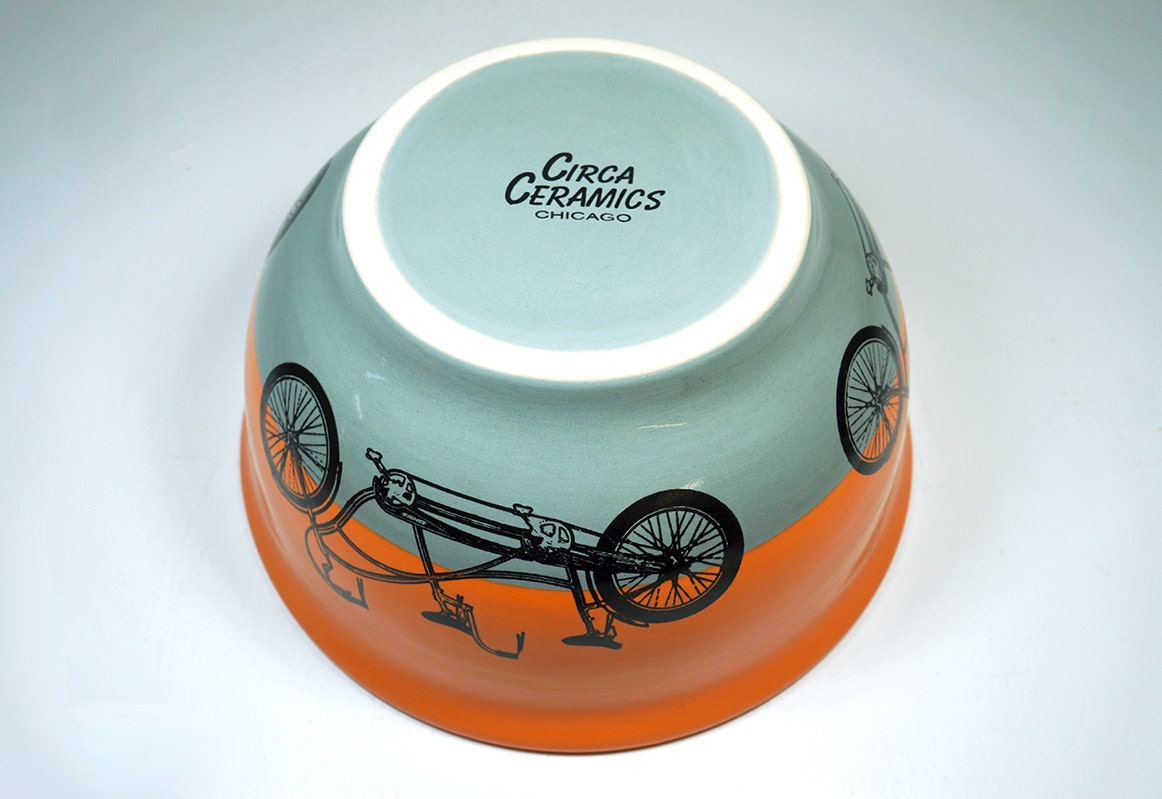 large bowl shown glazed in a colour block of Creamsicle & Storm with tandem bicycle prints. Made to Order.